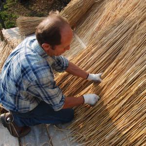 costruzione tetto in paglia, artigiano al lavoro